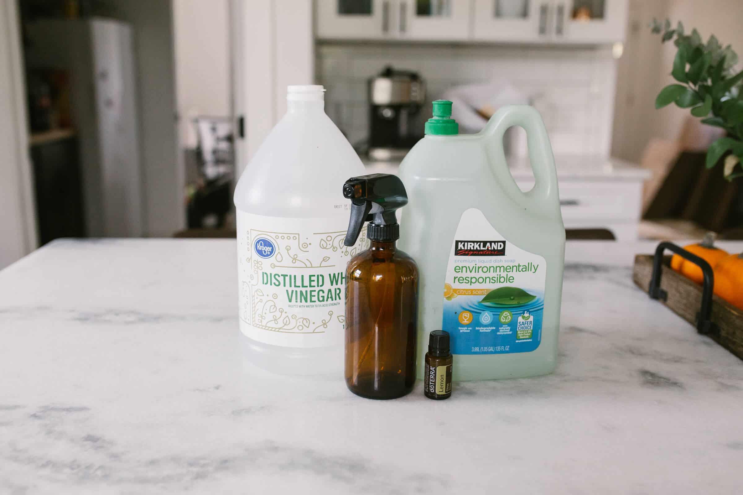 vinegar, dish soap, lemon essential oil, amber glass spray bottle on tope of white marble countertops in kitchen