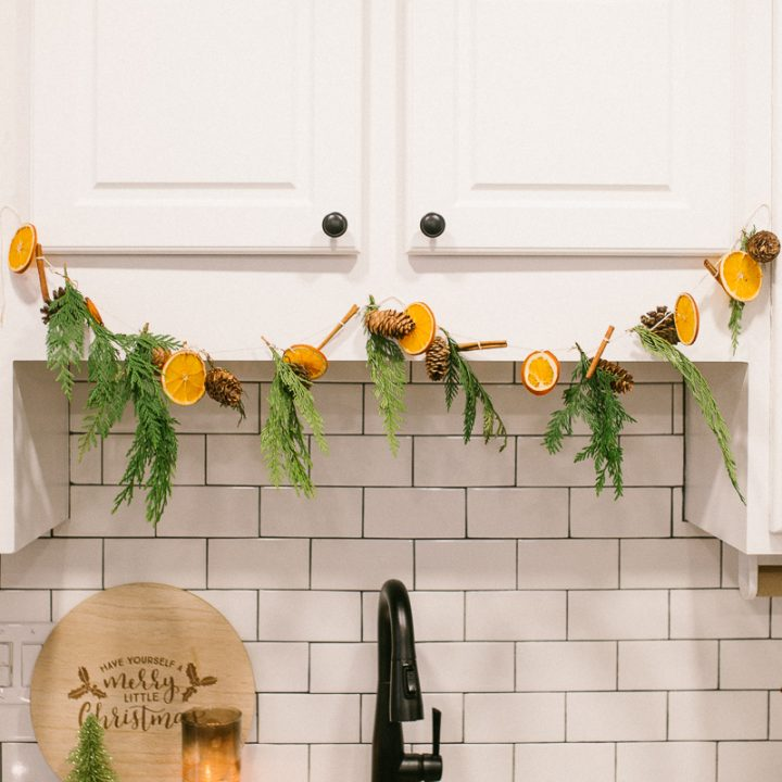 dried orange garland on a white cabinets with white subway tile