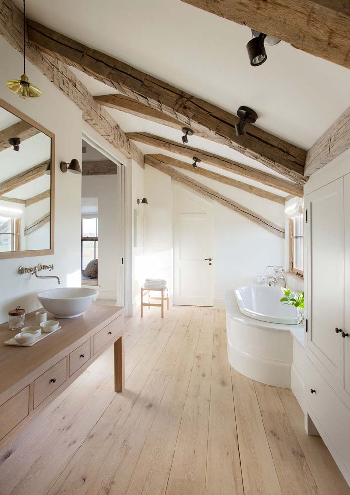 scandinavian bathroom with wood accents and a marble bathtub