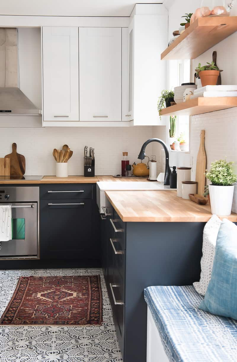 navy and white scandinavian kitchen with wood countertops and white back splash