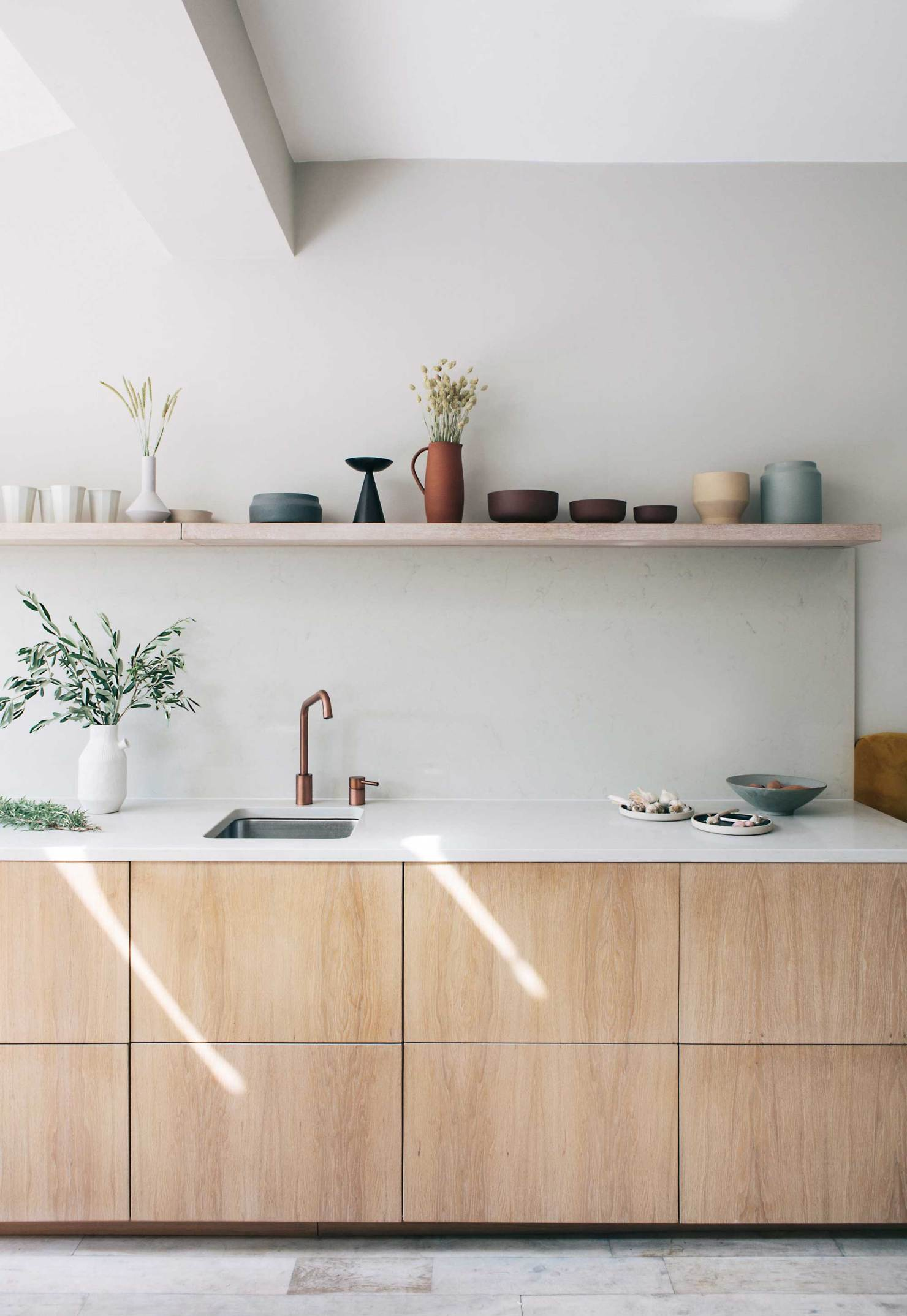 natural wood cabinets with a marble white countertops in a Scandinavian kitchen design