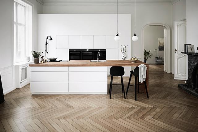 white scandinavian kitchen with herringbone wood floors and wood island