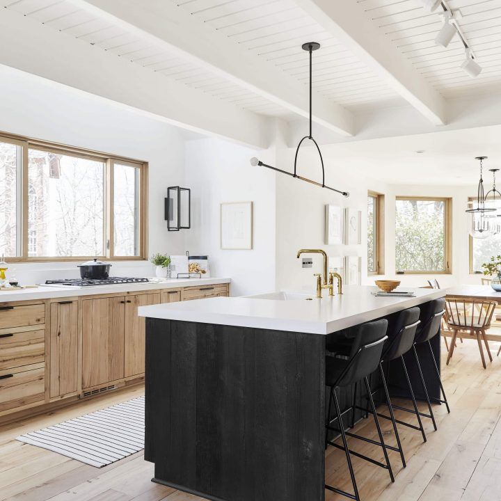 scandinavian kitchen with black island and wood cabinets