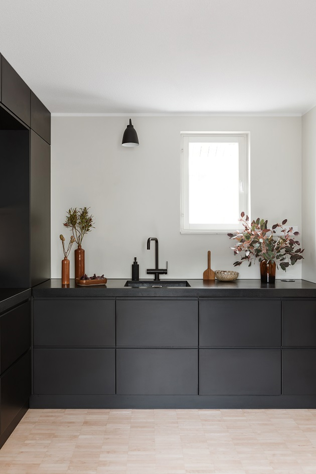 scandinavian kitchen with black cabinets and black countertops