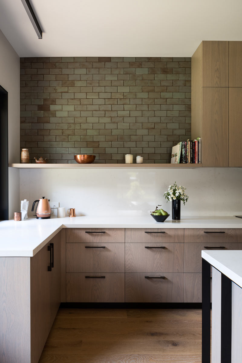 kitchen with wood cabinets, white countertops and a green brick backsplash