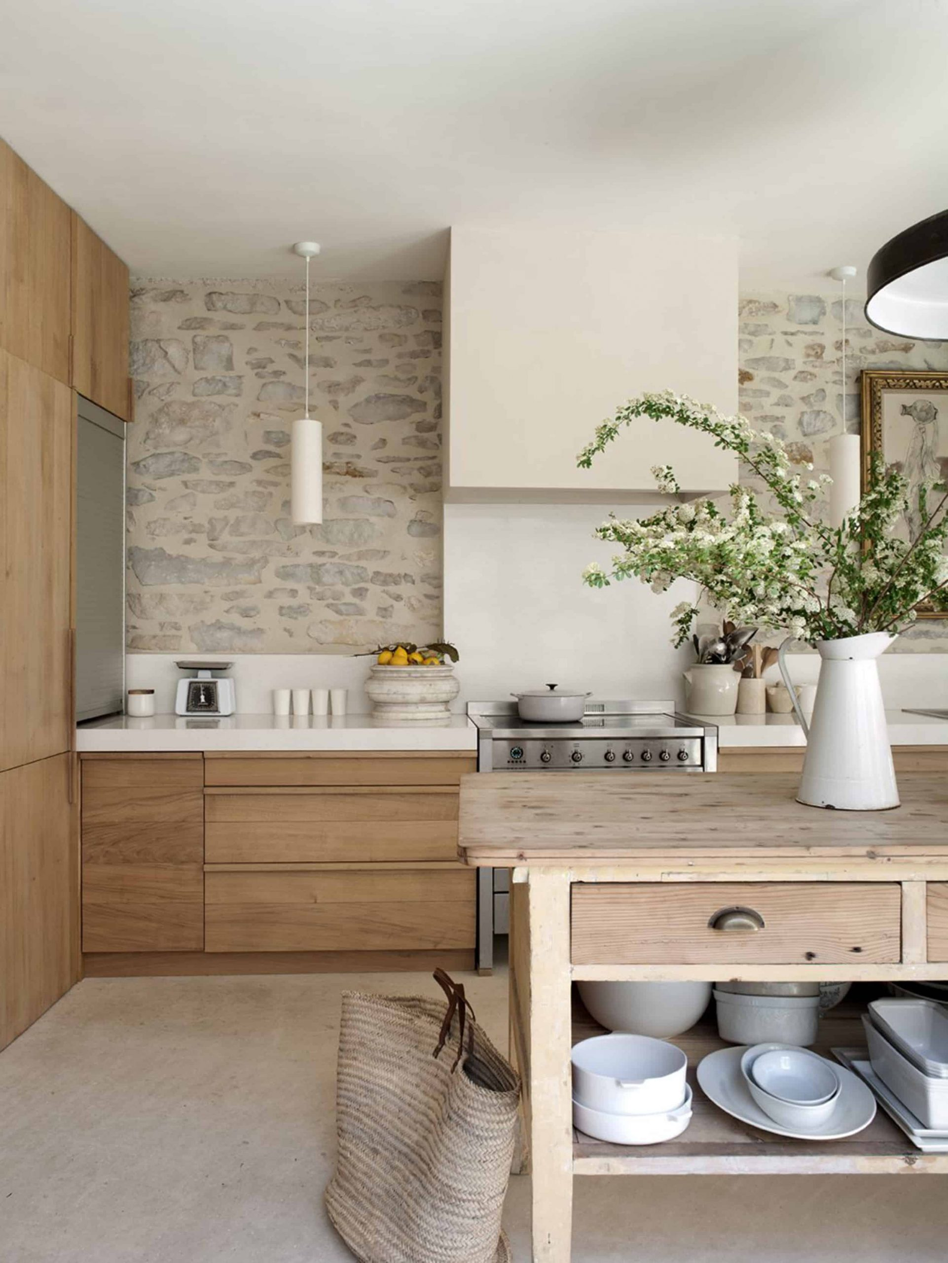 scandinavian kitchen with stone wall, wood cabinets and white countertops