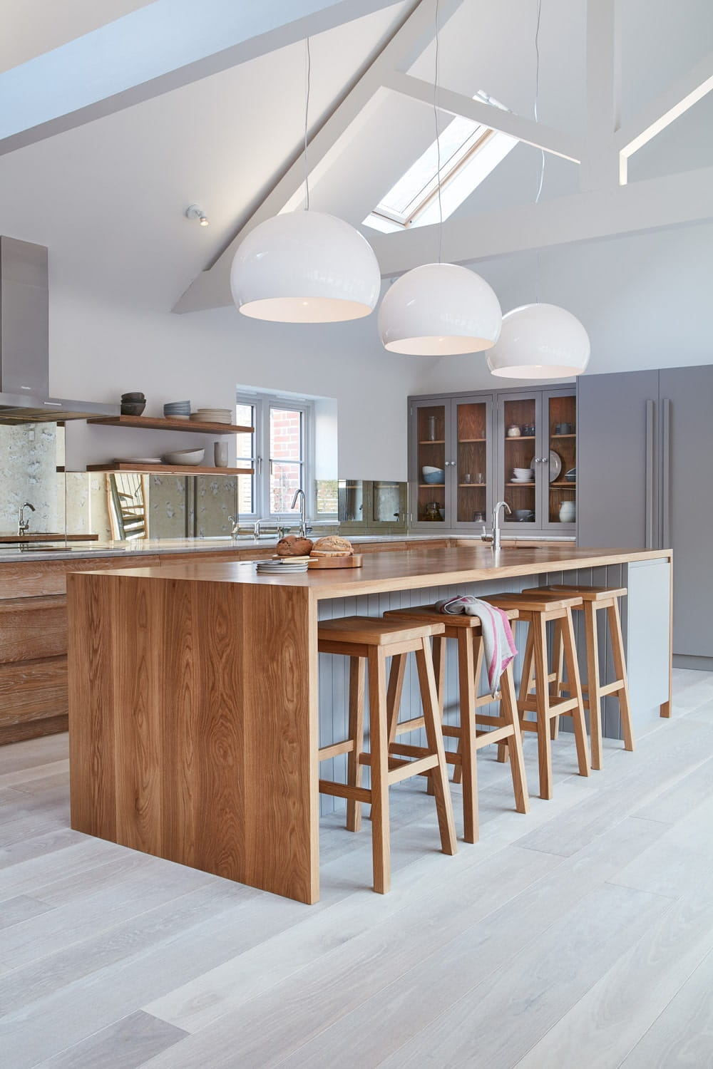 gray and white kitchen with globe pendant lights and wood waterfall island