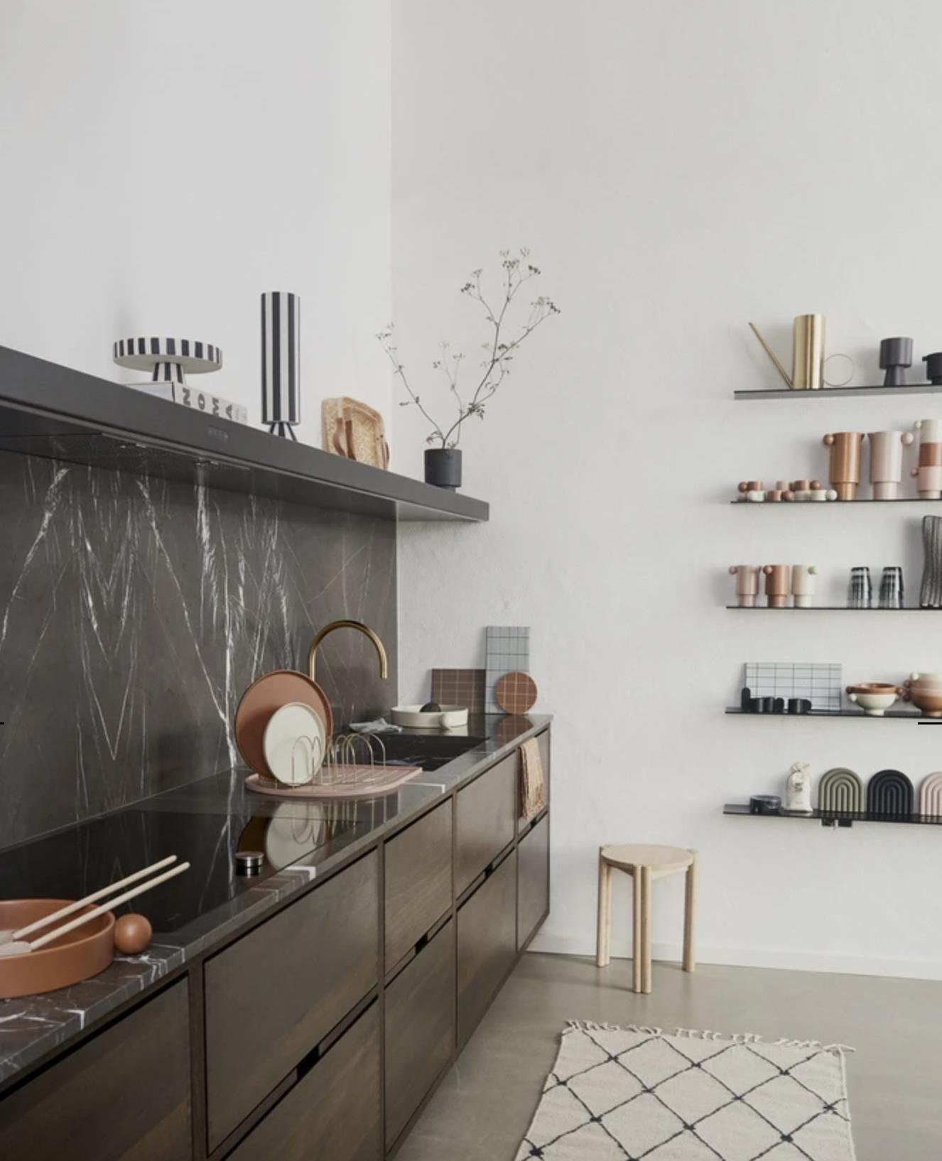 sleek dark brown cabinets with black backsplash in Scandinavian kitchen