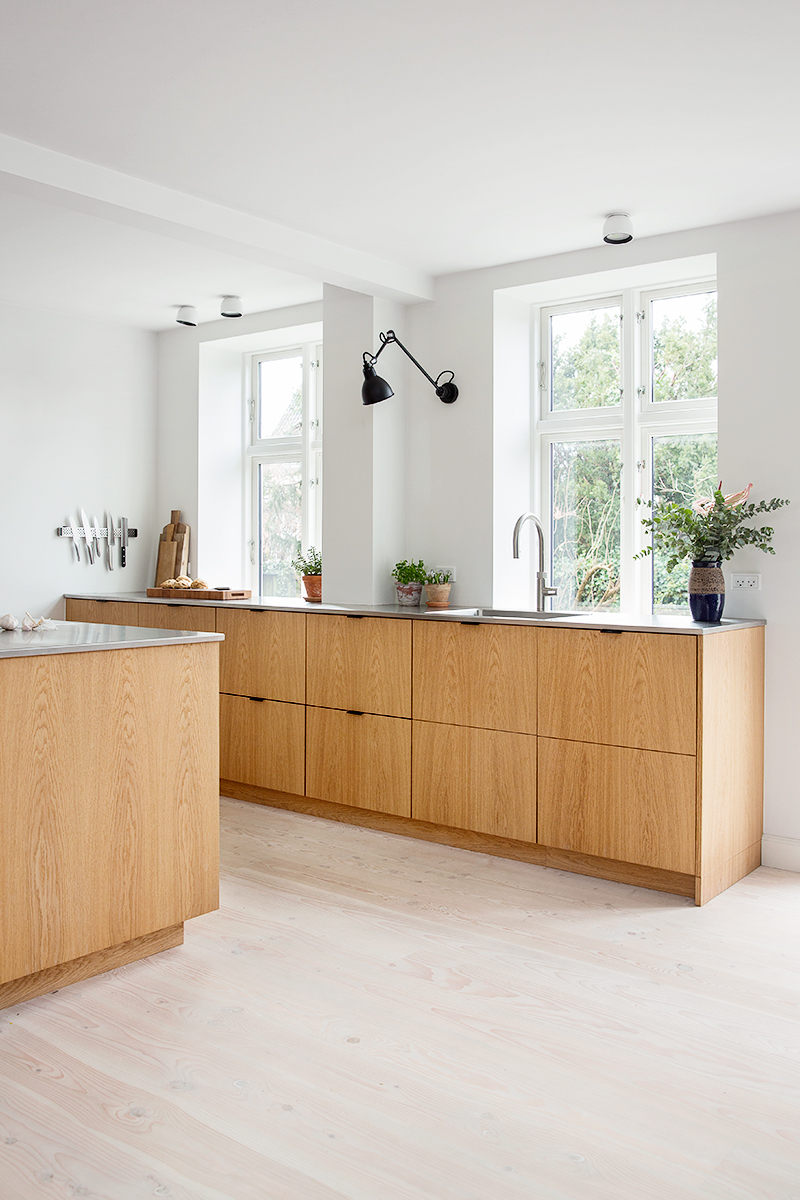 wood scandinavian kitchen with wood cabinets, gray countertops and black lights