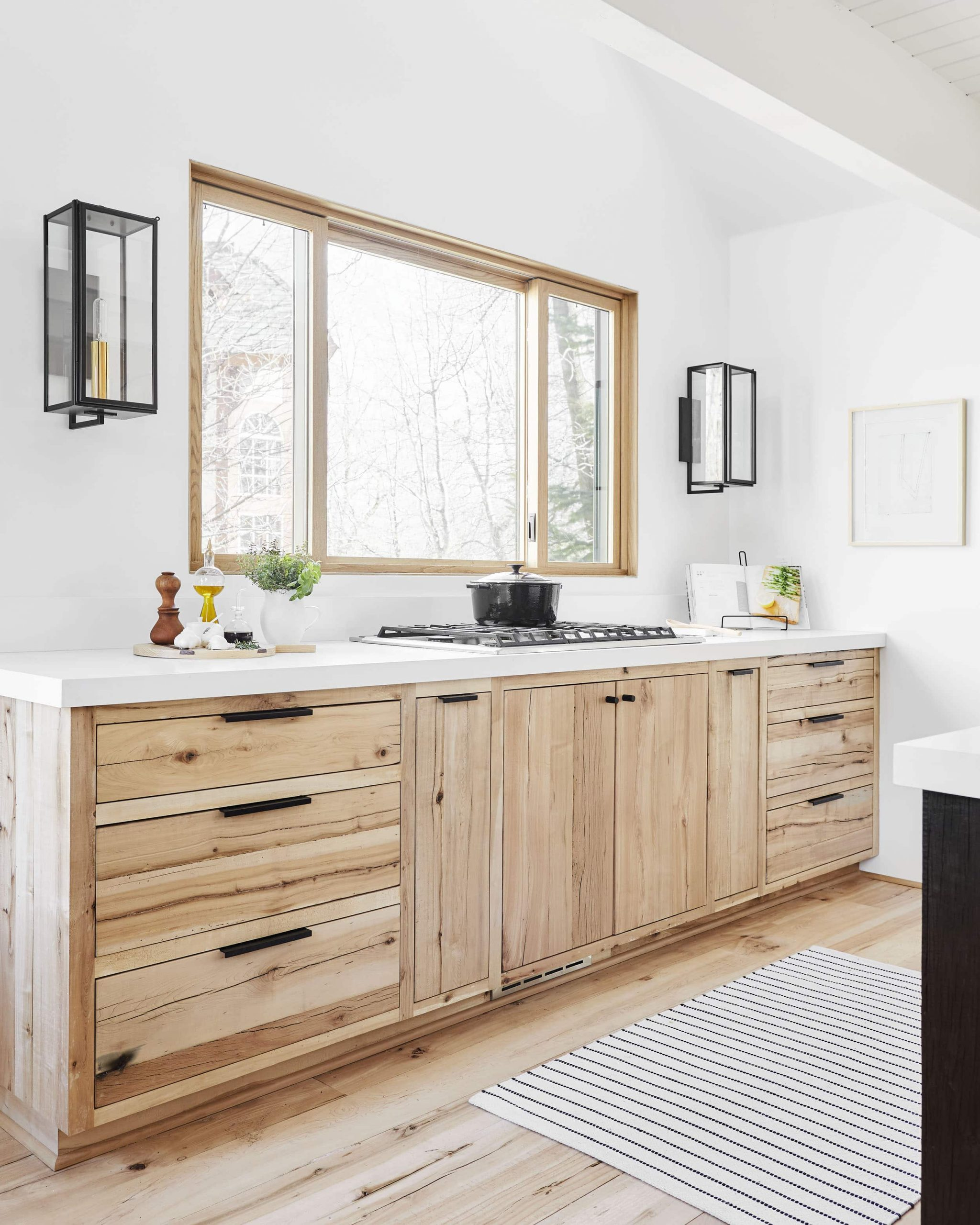 wood kitchen with black hardware and wood floors