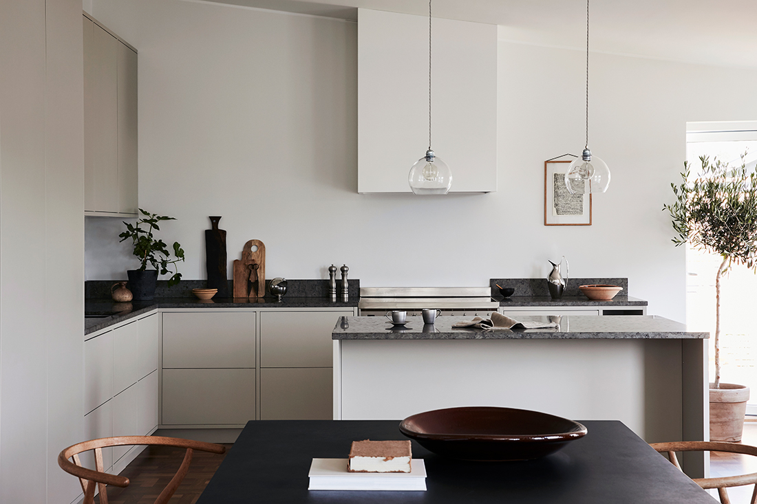 scandinavian kitchen with tan cabinets, black countertops, modern lights and black table