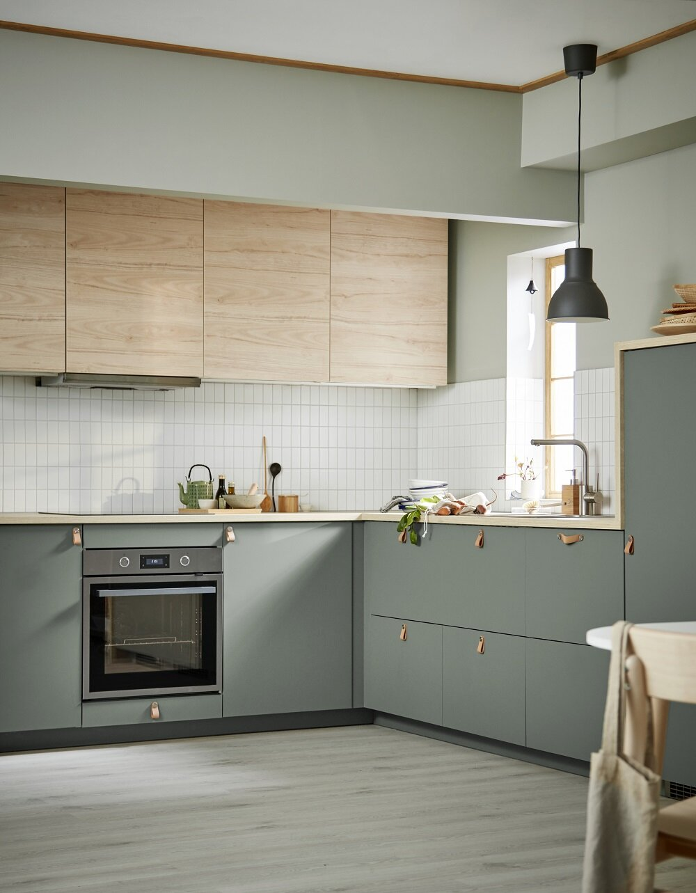 sage green cabinets and white subway tile back splash in a scandinavian kitchen