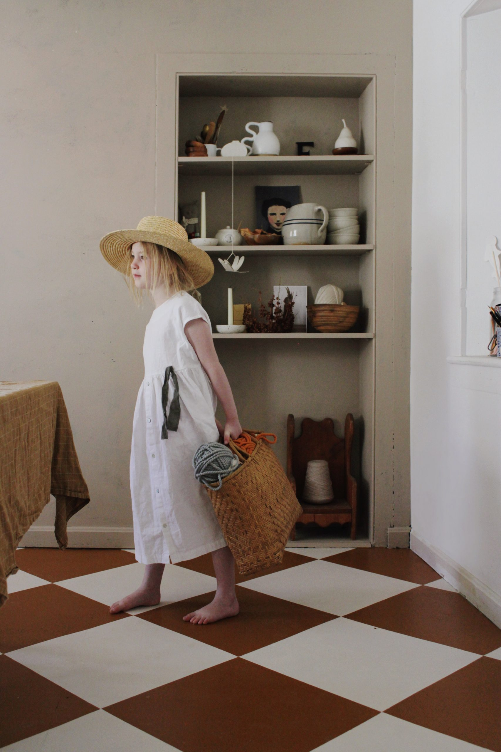 little girl in dining room with orange and white checkered tile floors