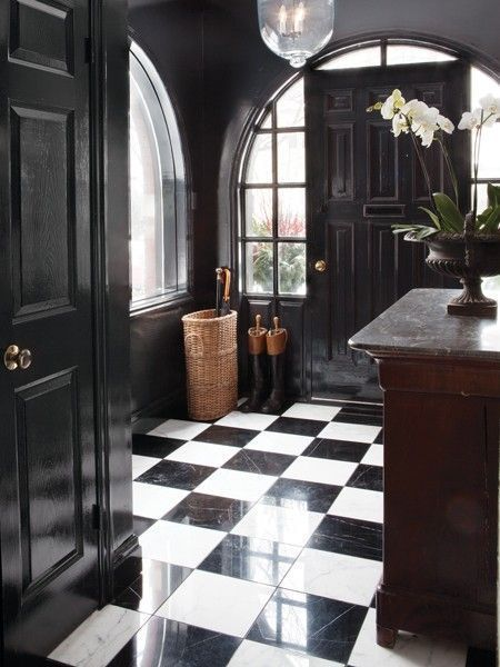 black entryway with black and white checkerboard floors and gold accents