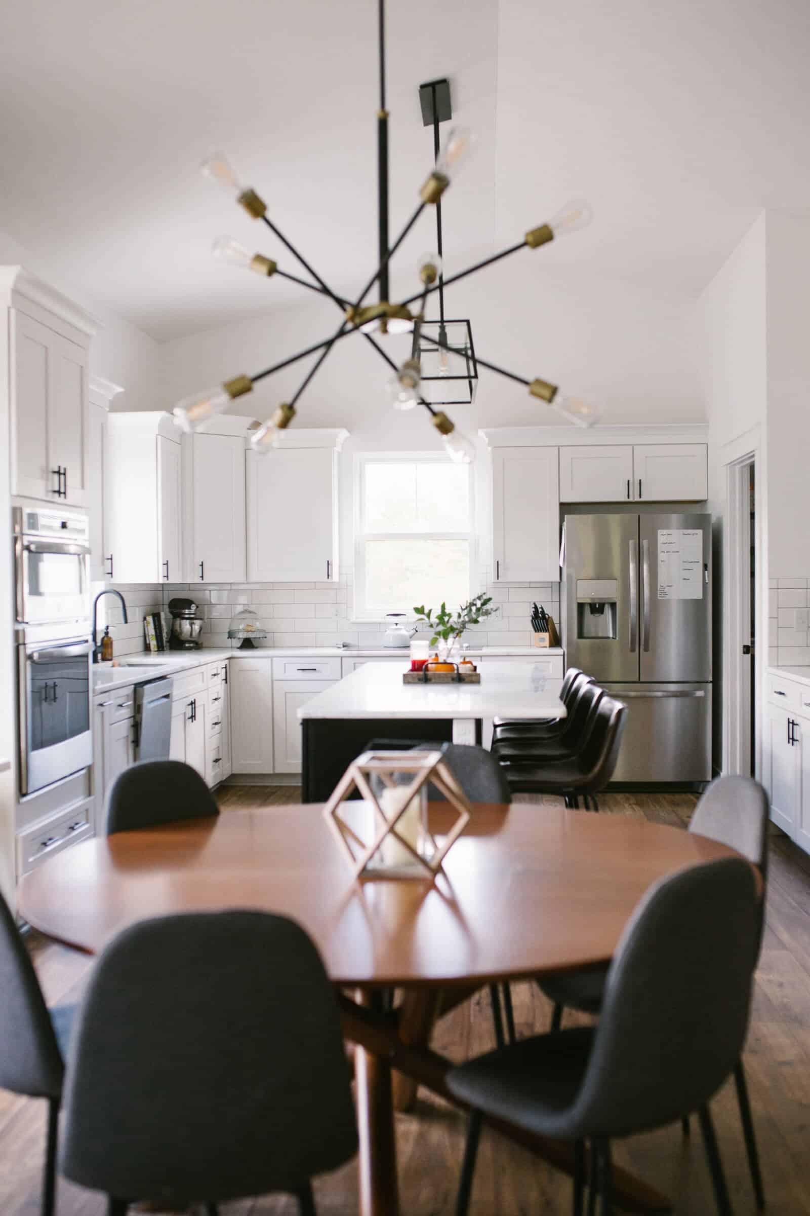 white modern kitchen design with white kitchen cabinets and a black island