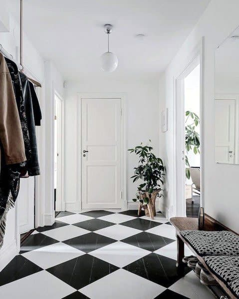 black and white wood checkered floors in entryway with all white walls and potted plant