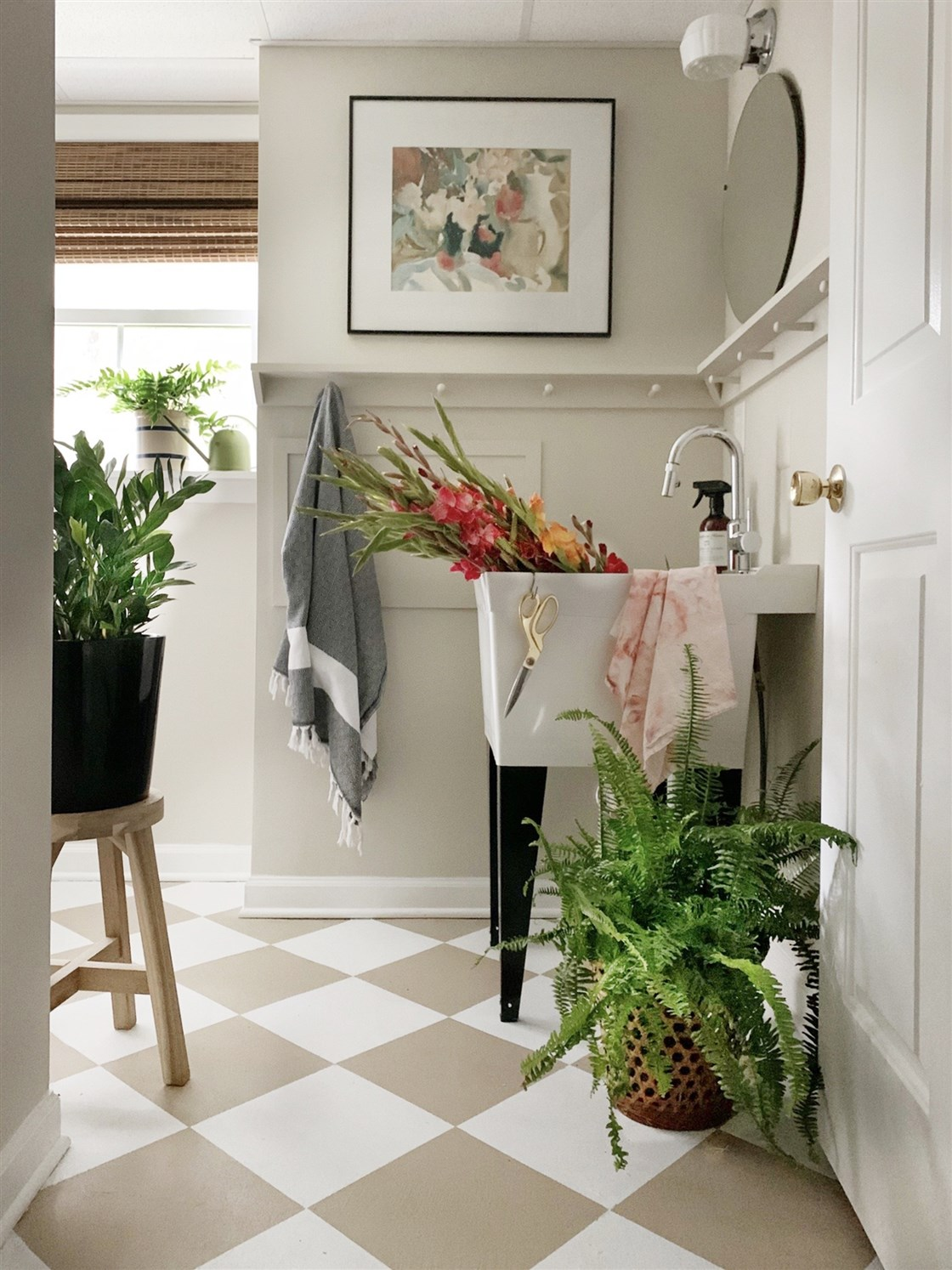 mudroom with tan checkerboard floors and green plants with tan walls and peg board wall