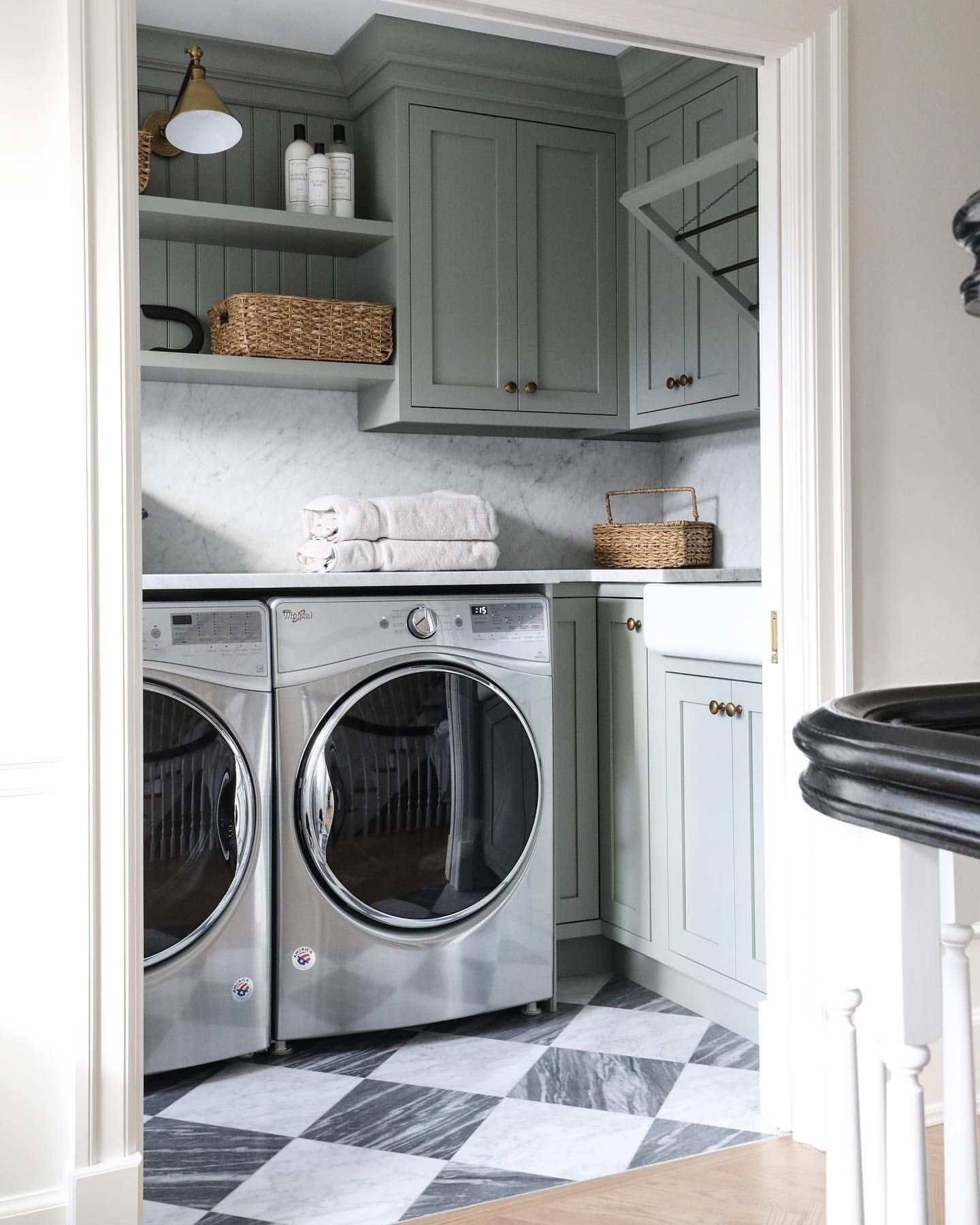 laundry room with whirlpool appliances with sage green cabinets and marble countertops