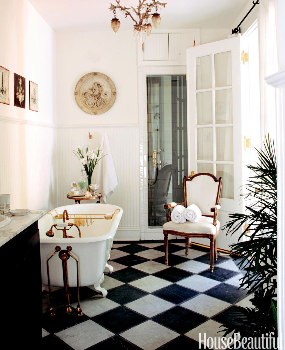 bathroom with white and black checkered floors with a claw foot tub and white walls