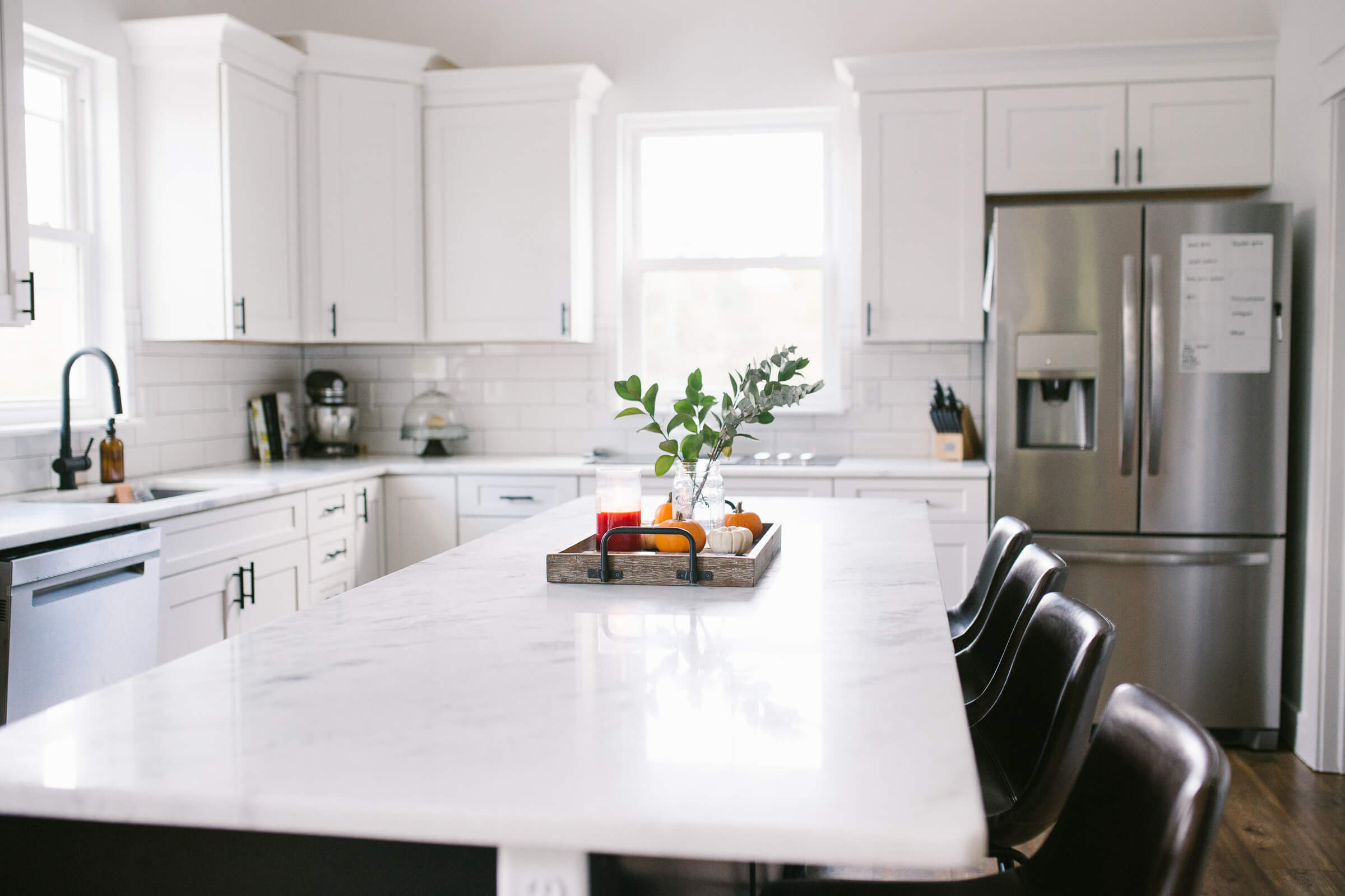 modern white kitchen with marble countertops and stainless steel appliances