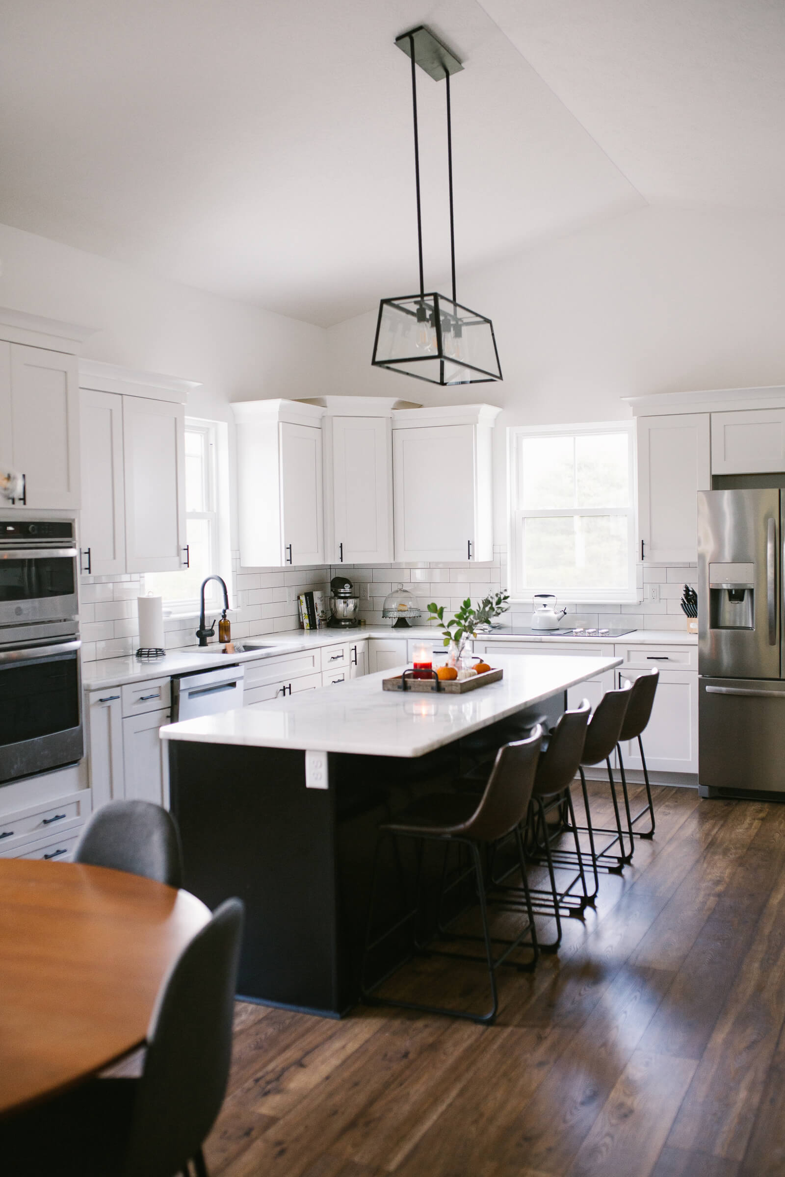 white kitchen with white cabinets and black island and brown leather bar stools