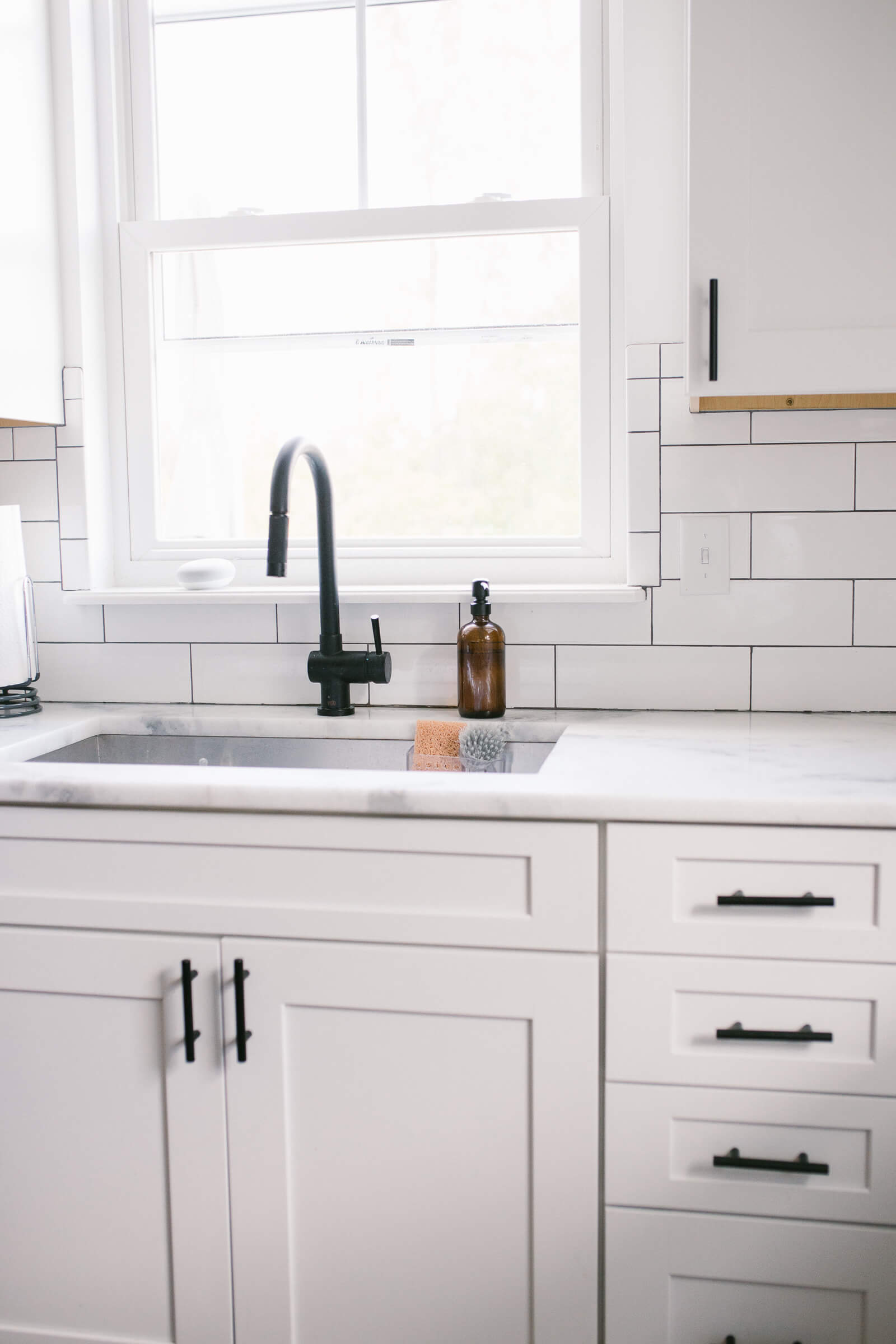white kitchen with black faucet and stainless steel sink