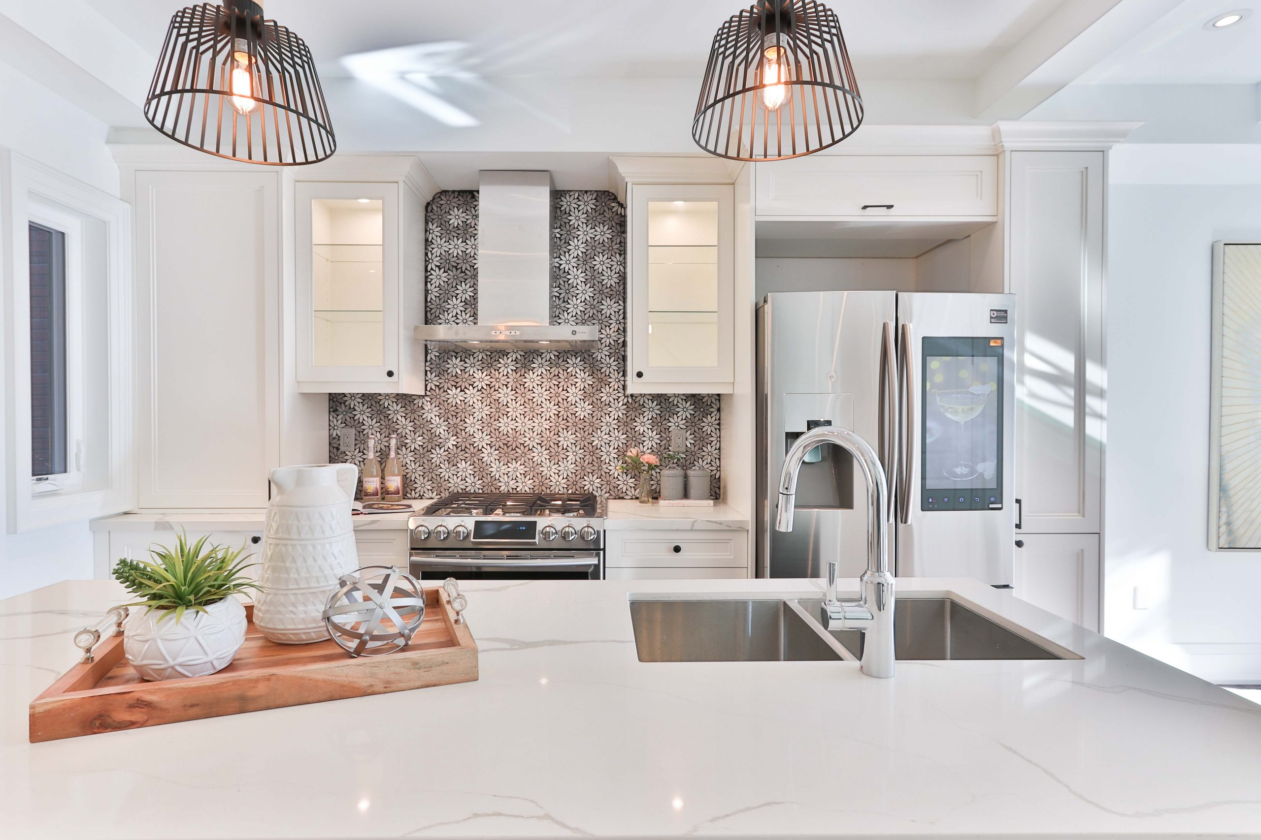 beautiful white kitchen with white marble countertops and white cabinets and a first time home buyer