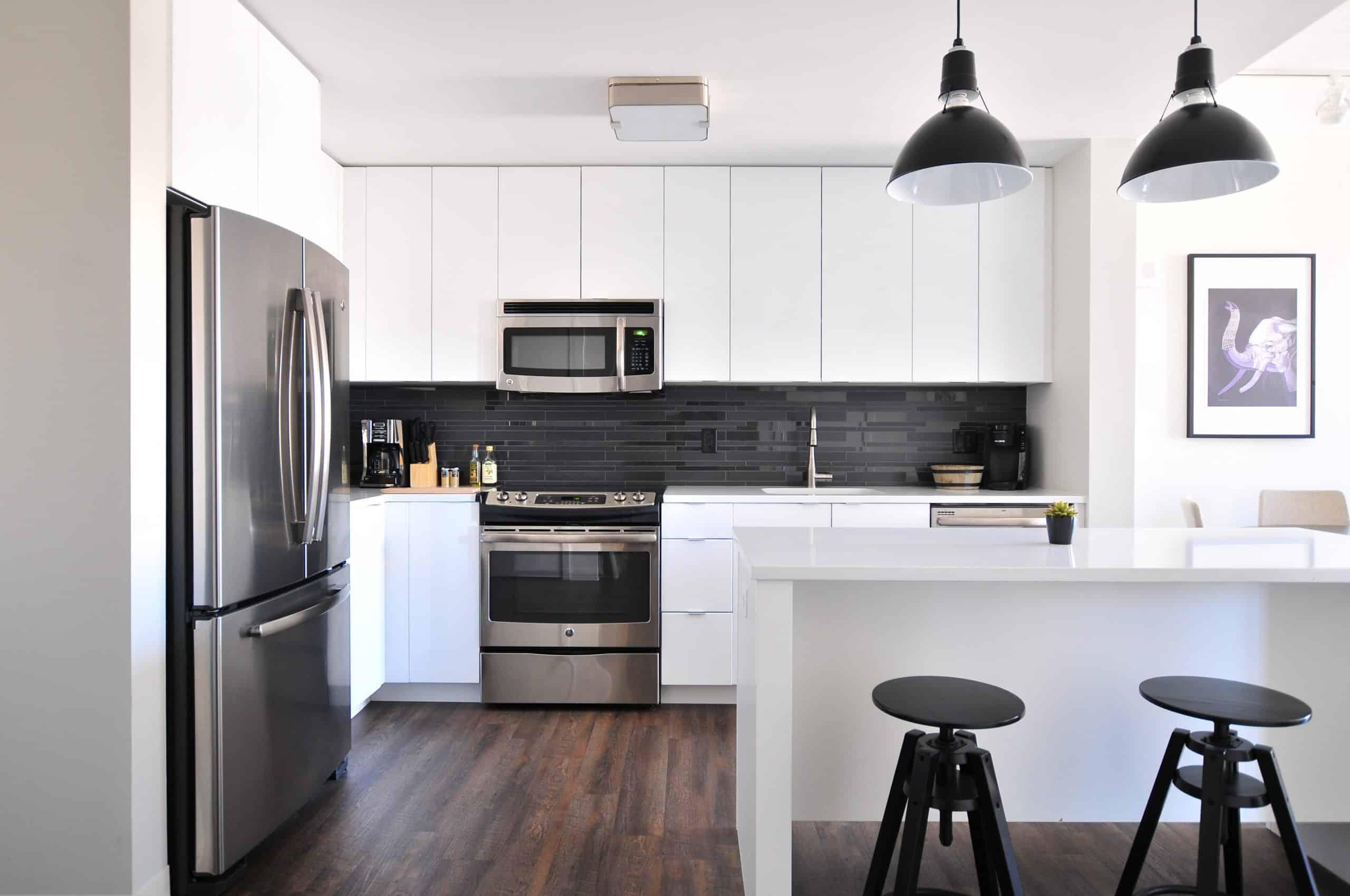 white kitchen with black backsplash and white countertops