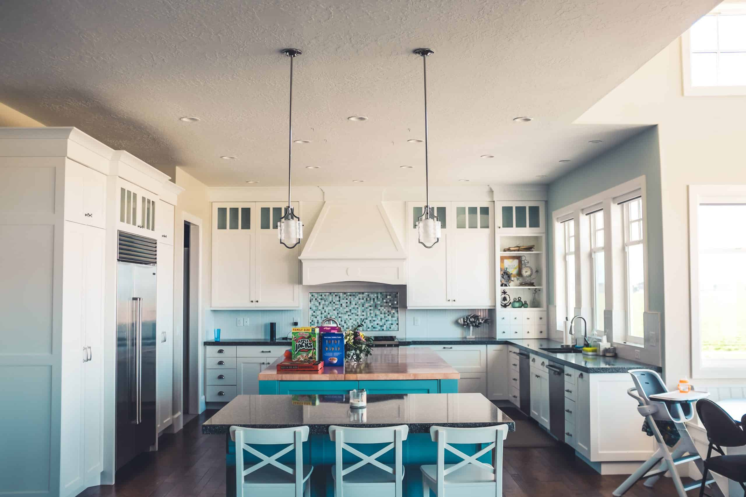 white kitchen with white cabinets and a turquoise island with a first time homebuyer