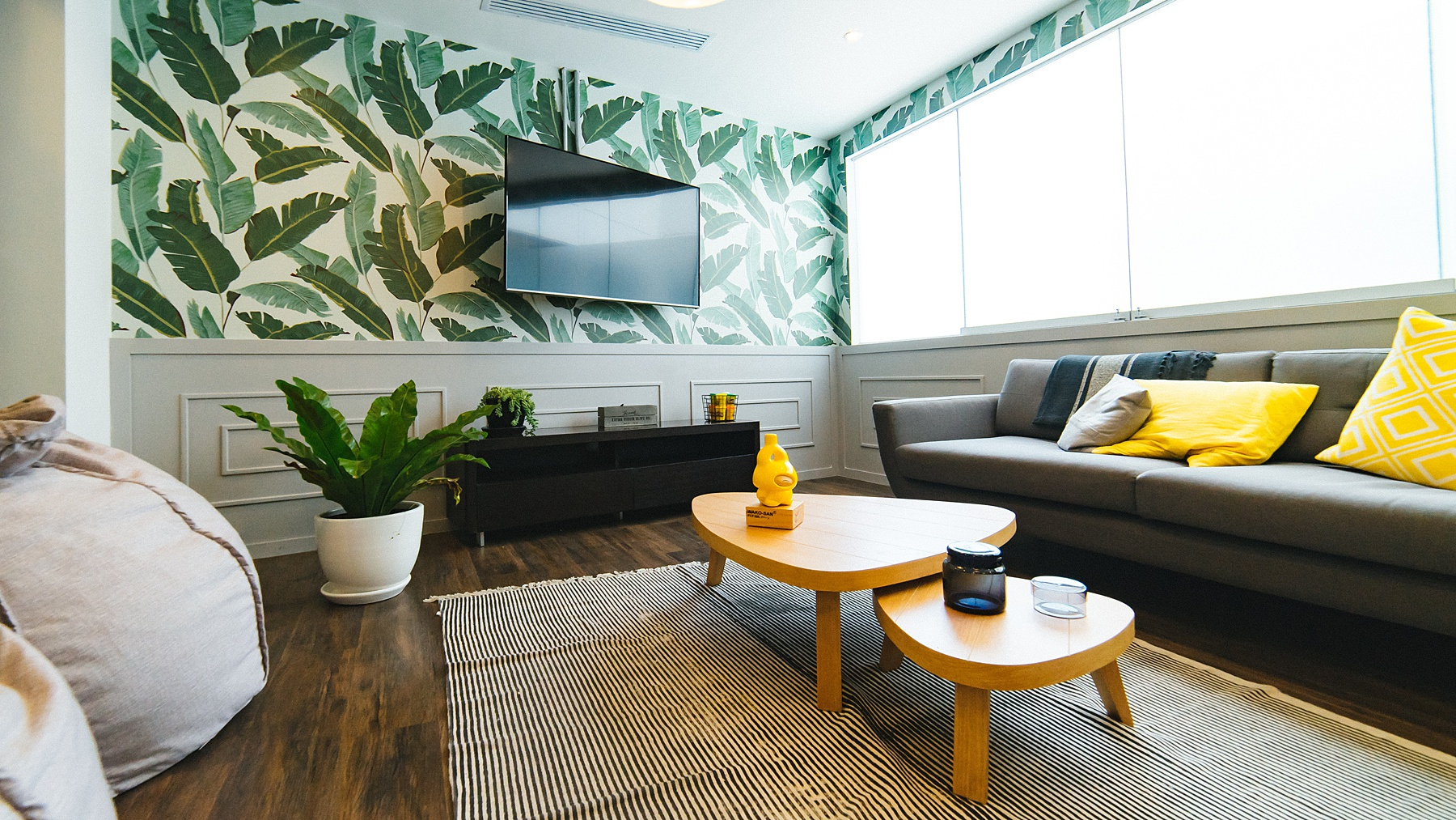 Living room with green leaf wallpaper, gray couch with yellow pillows for a pop of color-2021 Home Decor Trends
