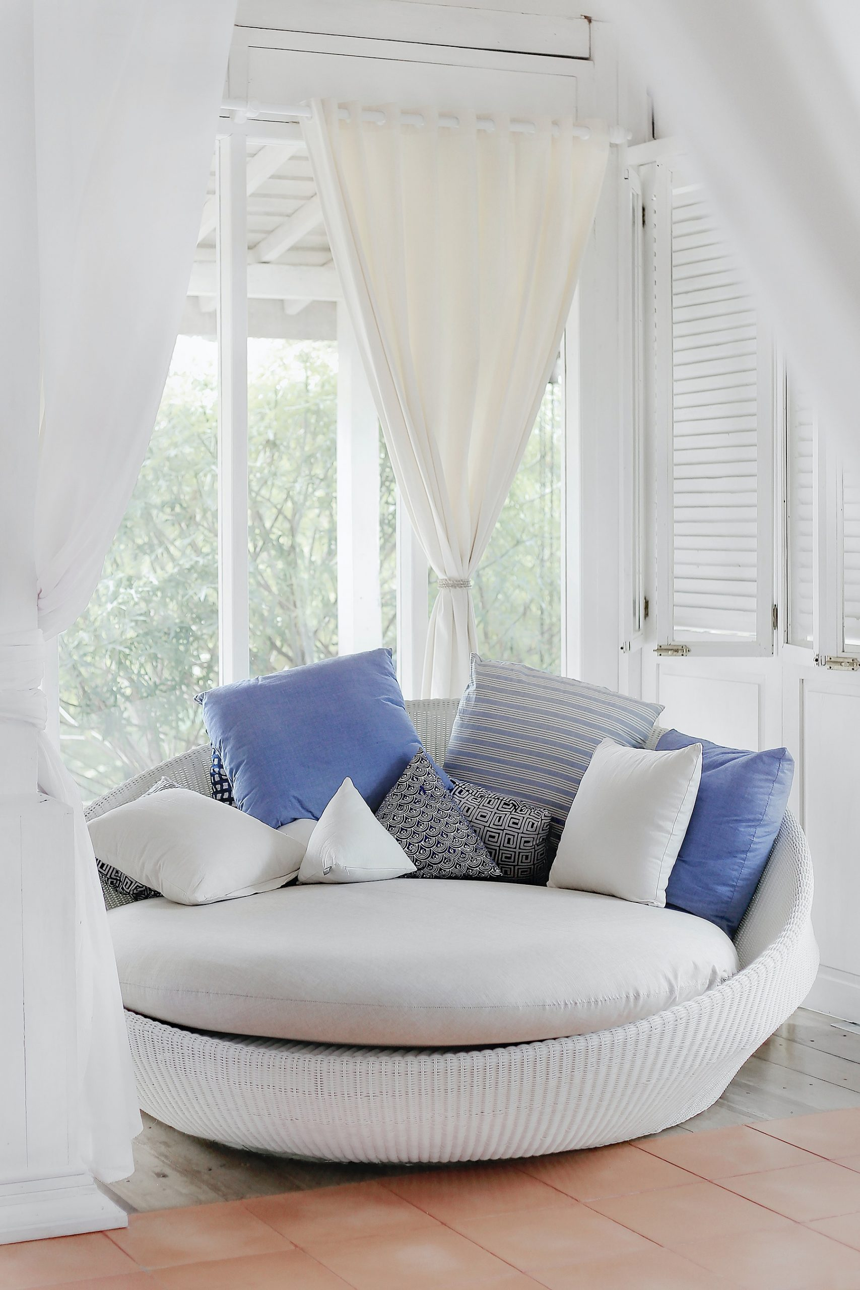 airy and calming nook of the home, with white curtains and comfy, round white seating accented with blue and patterned throw pillows