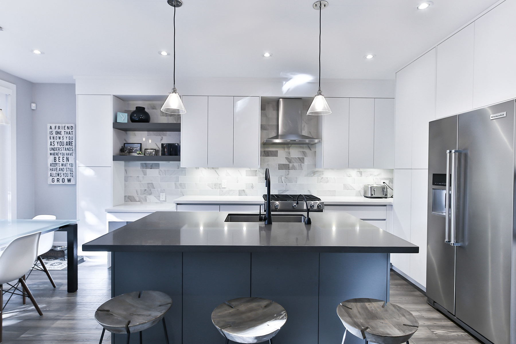 Kitchen with two-tone cabinets- white cabinets and countertop along the wall and dark blue cabinets and black countertops featured on the island- 2021 Kitchen Design Trends
