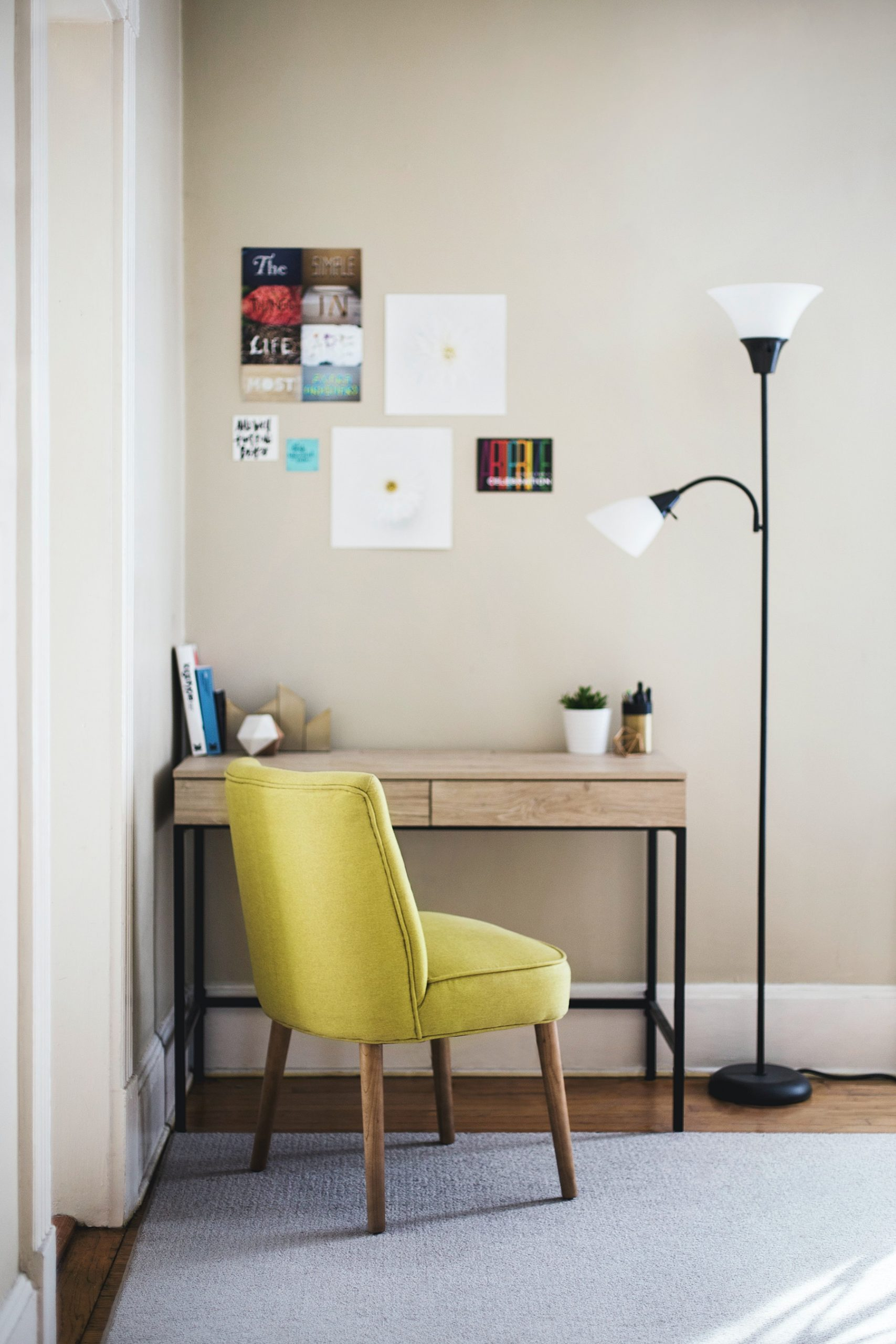 Small desk in corner with comfy chair in a pop of color and simple lighting