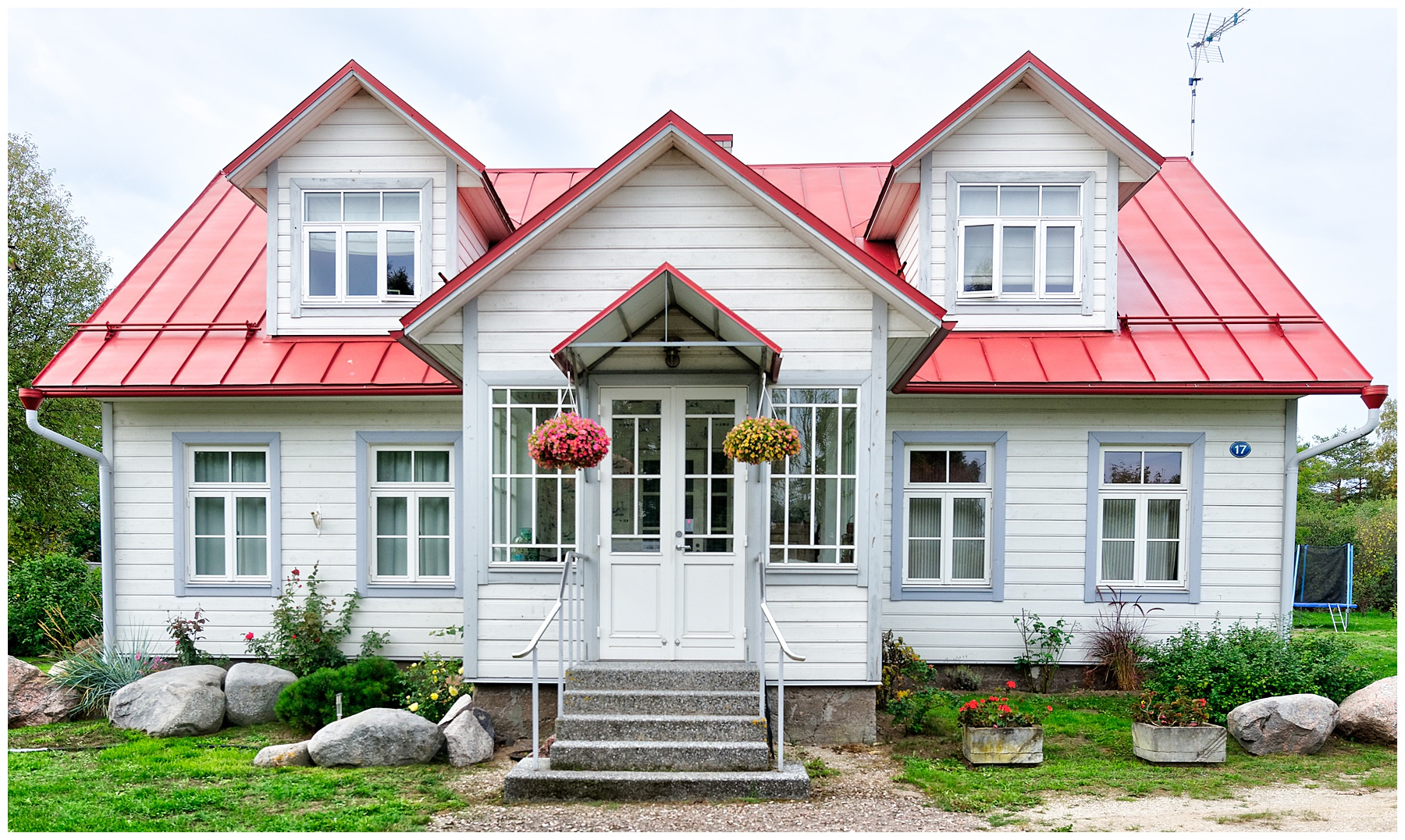 Exterior of a home with red tin roof and planters by the from door. Images for whether you should buy or build a home.