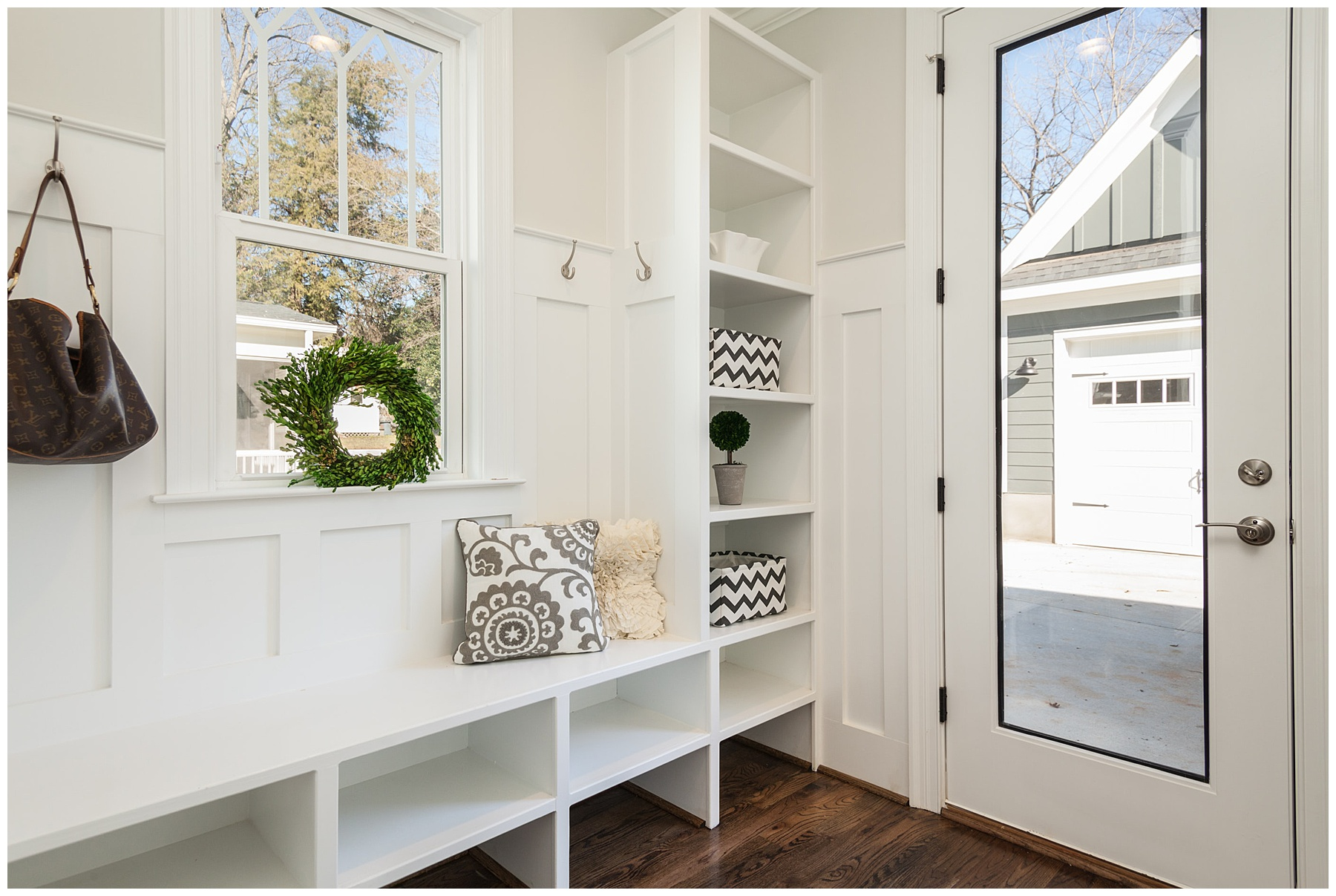 Large mudroom with bench seating and storage shelves for shoes, jackets, etc.