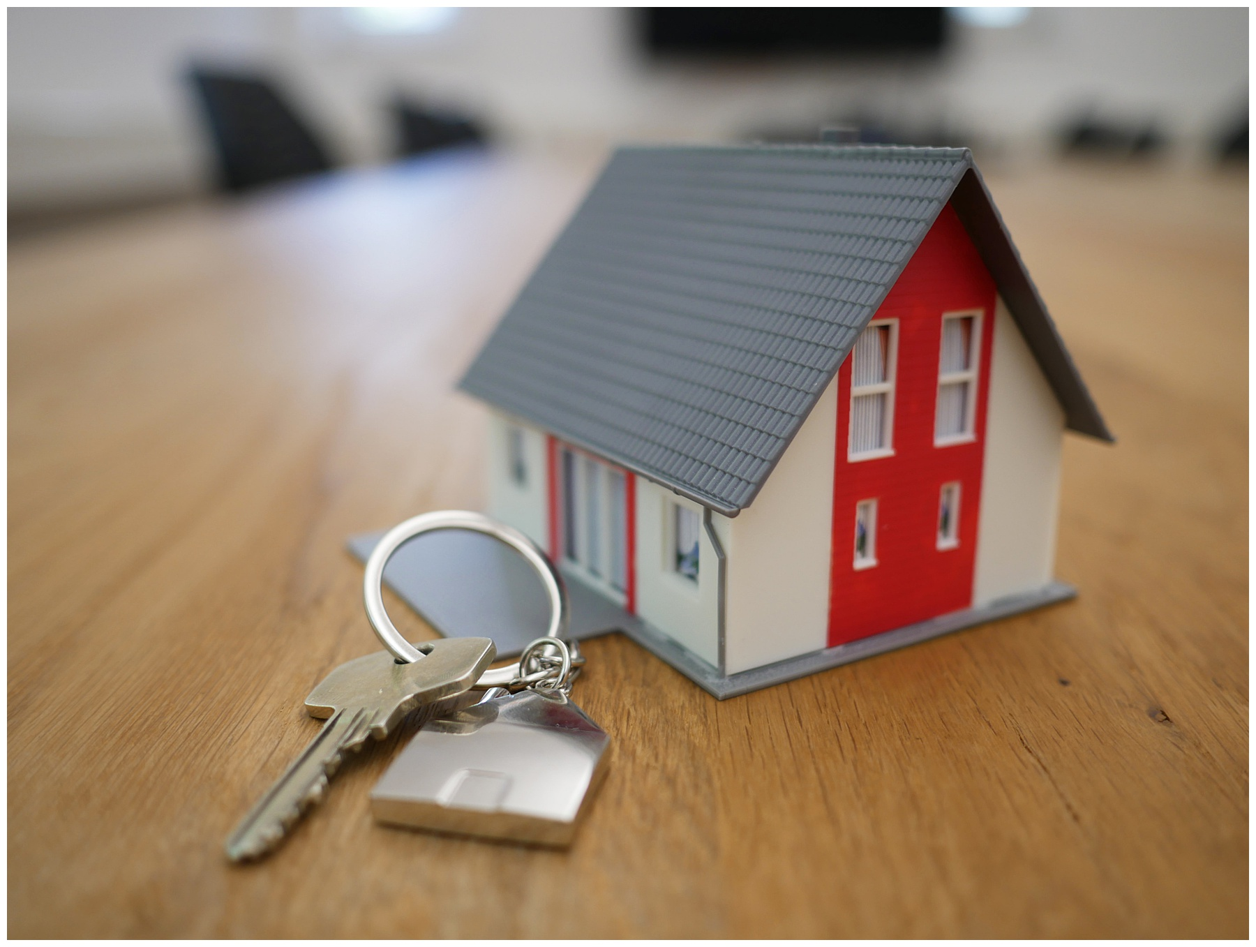 Picture of small house model and a key for a new home to symbolize buying a home in a seller's market