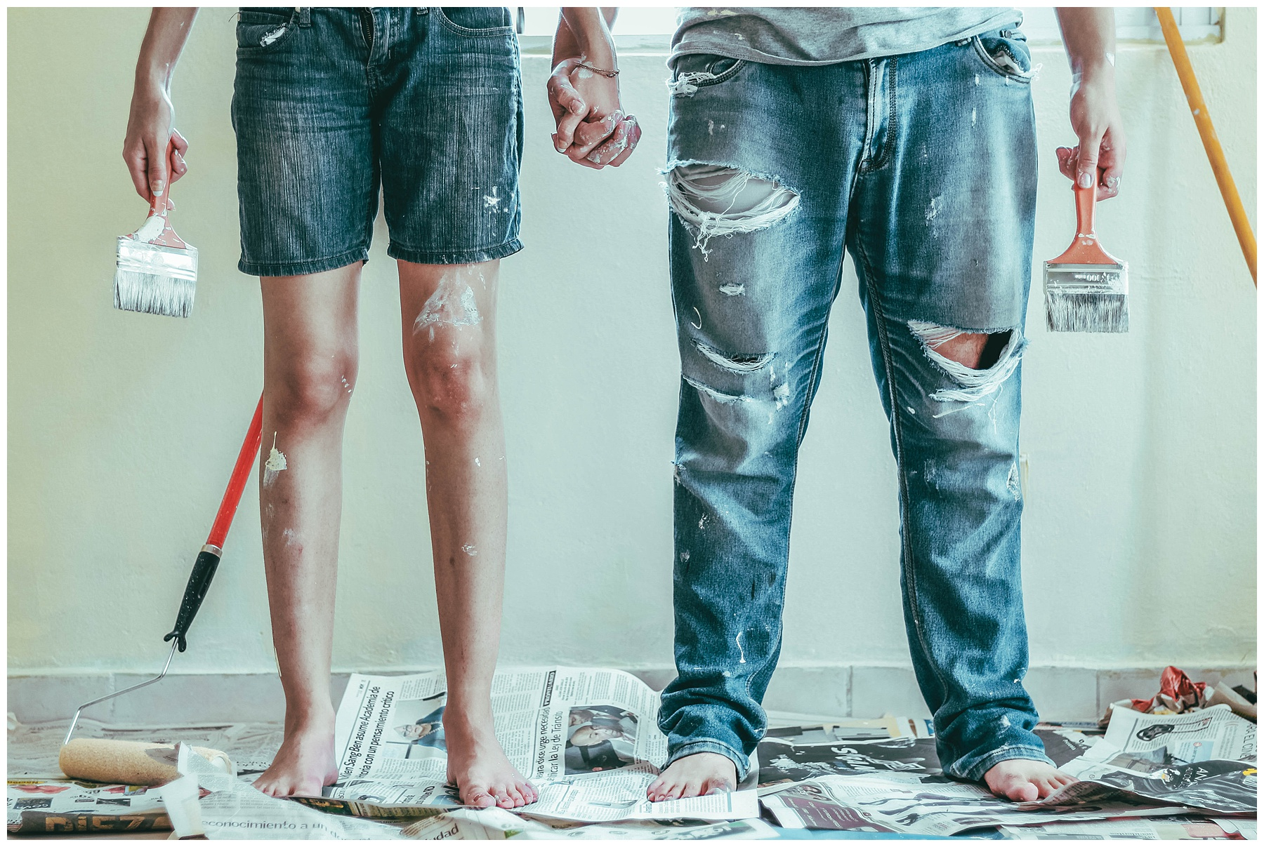 cropped picture from the waist down of a couple holding hands and paint brushes while standing on newspapers covered in paint for a home remodel