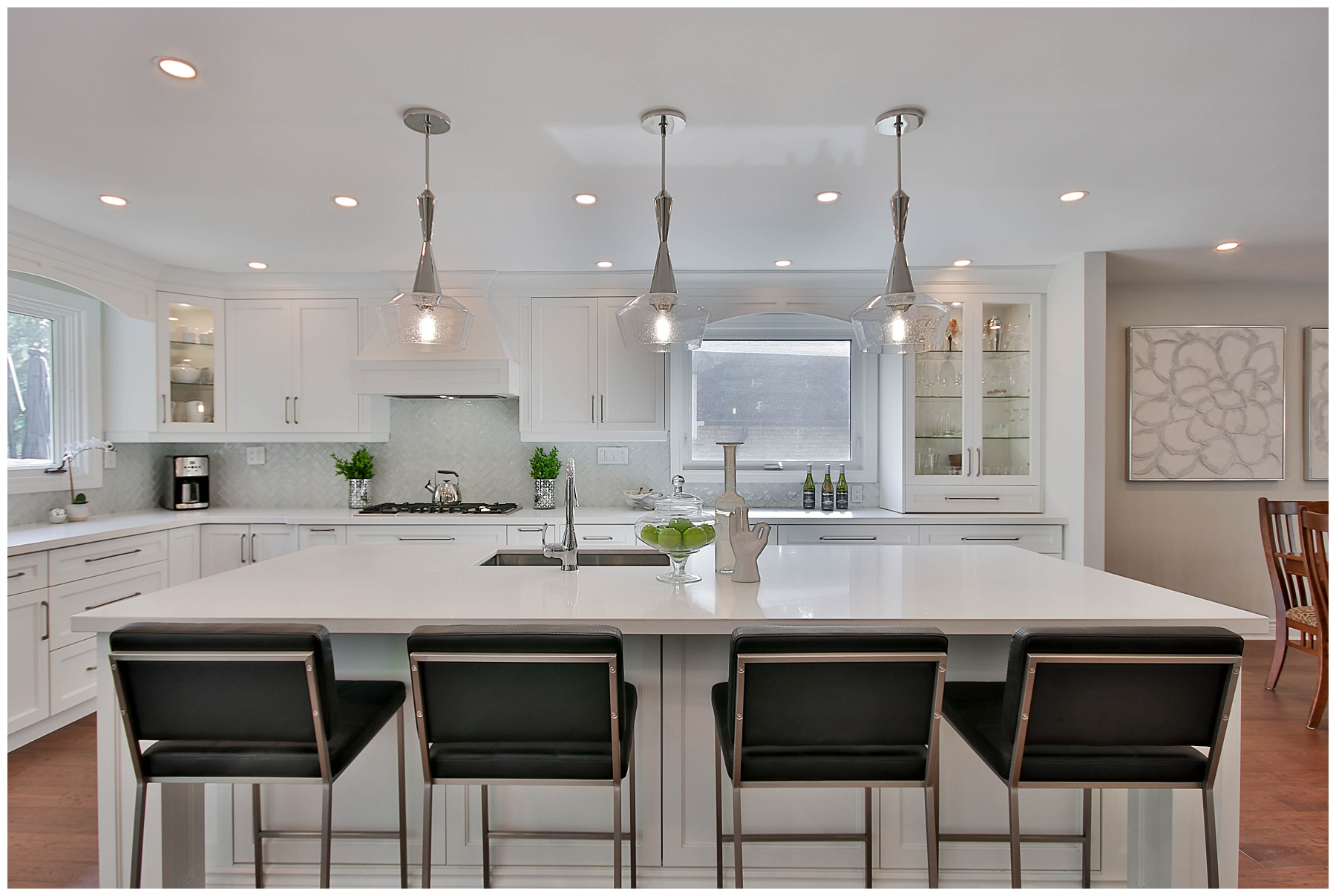 A beautiful open concept kitchen with large island, white cabinets, and black seating