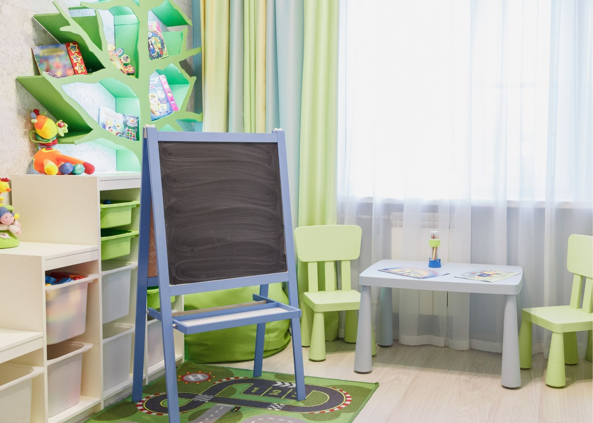 Kids play space with table, easel, and toys.